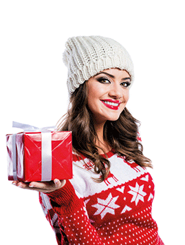 A woman in a festive jumper with a wrapped gift