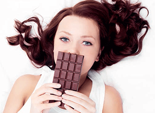 A young woman with a bar of chocolate