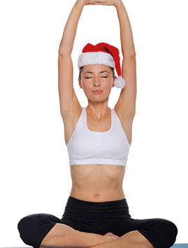 A photo of a woman doing yoga in a santa hat